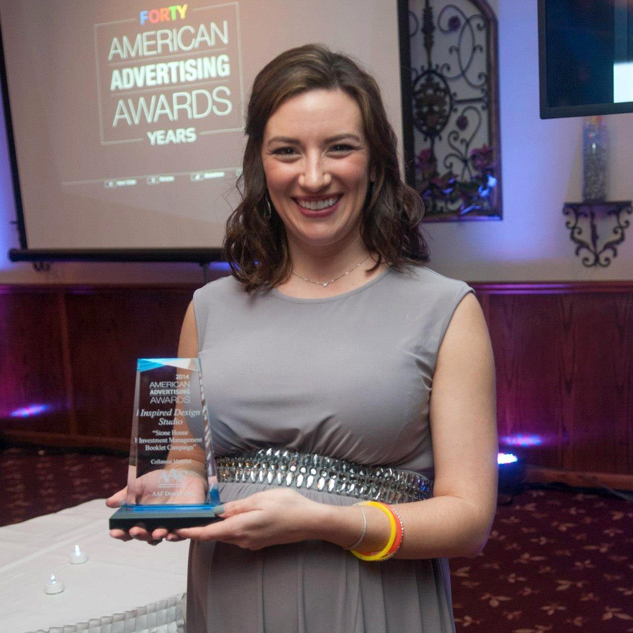 Maria Traino holding American Advertising Federation 2014 Silver Award for Stone House Investment Management Booklet Campaign
